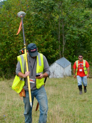 Mike Tripp/The News Leader A Dominion route survey team member checks his phone as he walks with a sub-centimeter GPS unit across the field his team just surveyed. A contracted employee with a two-man Dominion route survey team  checks his phone as he walks with a sub-centimeter GPS unit across the field his team just surveyed near Guthrie Road on Friday, Sept. 12, 2014. They help survey the route for the DominionÃ?s proposed natural gas pipeline.