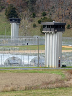 Guard towers loom over Augusta Correctional Center's fence in Craigsville.
