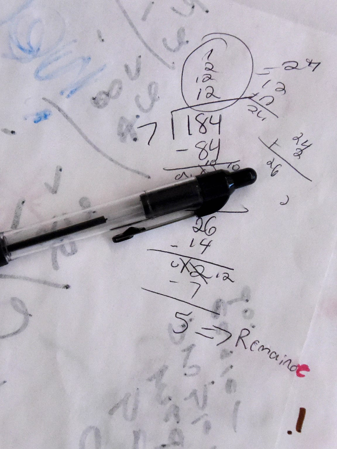 A pen rests on top of a paper marked numbers and equations