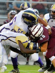 Waynesboro's Jaquarius Chambers and Michael Brown wrap up Stuarts Draft's John-Mark Burnett who runs the ball during the first half of a football game played in Stuarts Draft on Friday, Sept. 12, 2014.
