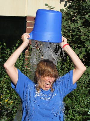 Meg Posorske pours water over her head in the ice bucket challenge for the Amyotrophic Lateral Sclerosis(ALS) Society at the Aurora Medical Center participated Tuesday. The group wants this challenge to send a message out for those with ALS and their families.
