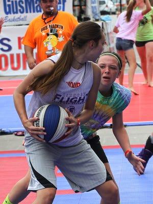 A Oshkosh Flight player looks to pass against the Terror's Force team as Main Street in Oshkosh hosted the three on three Gus Macker Basketball Tournament over the weekend.