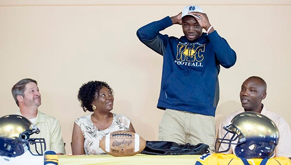 Adetokunbo Ogundeji, of Walled Lake Central, places a Notre Dame cap on his head after announcing that he will be attending the school to play football. Joining him are Walled Lake Central coach Bob Meyer, and parents Anthonia and Oladapo.