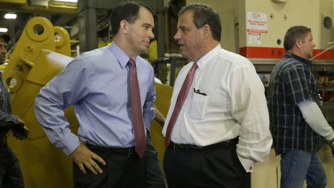 Wisconsin Gov. Scott Walker, left, backs the Green Bay Packers. New Jersey Gov. Chris Christie, right, likes the Dallas Cowboys.