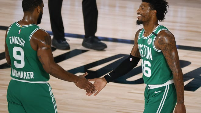 Boston Celtics' Marcus Smart, right, celebrates a 3-point shot with Brad Wanamaker during the fourth quarter against the Philadelphia 76ers in Game 2 of an NBA basketball first-round playoff series, Wednesday, Aug. 19, 2020, in Lake Buena Vista, Fla.