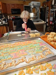 Christine Suhre-Garza decorates holiday cookies, while in the kitchen of her Poughquag home Nov. 15, 2017.