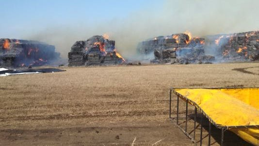 Bales of stover burn at the DuPont Danisco storage site March 31. About 5,200 bales were destroyed in the blaze, which threatened a nearby home.