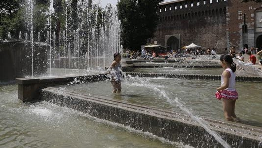 Children play in a fountain in front of the Sforza Castle, in Milan, Italy, on June 10, 2014.