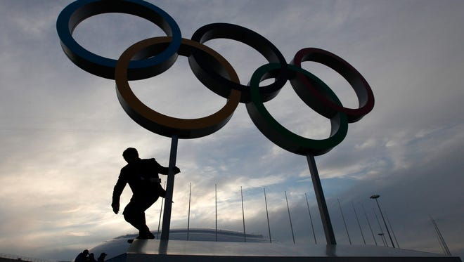 A man steps down from a platform displaying the Olympic rings as preparations continue for the Sochi Winter Olympics.
