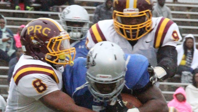 Pearl River linebackers Randy Hogan (8) and Jarkeith Ruffin (9) team up to bring down Co-Lin running back Lakedric Lee during junior college football action Saturday at Wesson.