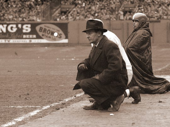 Cleveland Browns coach Paul Brown kneels on the sideline during a game on Dec. 6, 1953. In this position Brown is the club's second quarterback, calling virtually all signals as he sends in instructions via guards Lin Houston and Chuck Noll (both not pictured). At Brown's right is George Ratterman, reserve quarterback. Location is unknown. (AP Photo)