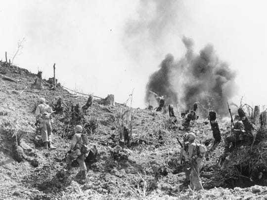 With Japanese grenades exploding around them, U.S. Marines move up a hill on Skyline Ridge.