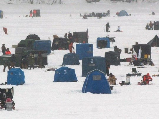 Ice fishermen, most in shelter from the cold and wind,