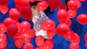 Democratic presidential nominee Hillary Clinton reaches toward the falling balloons at the conclusion of the Democratic National Convention in Philadelphia, Thursday, July 28, 2016.