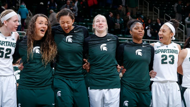 Michigan State players, including from left, Becca Mills, Jasmine Hines, Madison Williams, Kelsey Kuipers, Branndais Agee and Aerial Powers celebrate following their game against Illinois Thursday, Jan. 15, 2015, in East Lansing, Mich. Michigan State won 63-56.