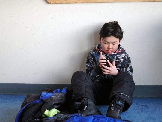 A young boy checks a cell phone while waiting for a