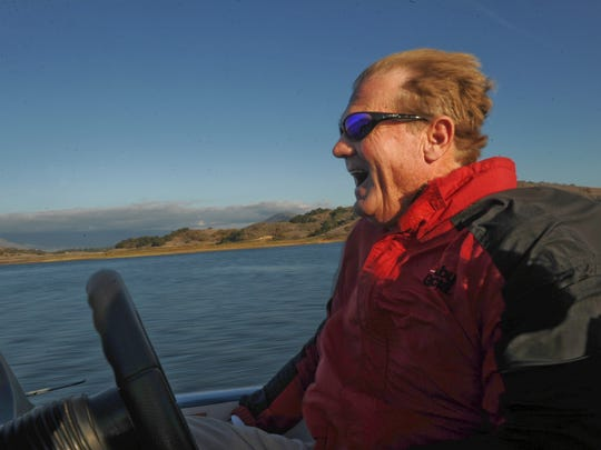 In a 2012 photo, fishing guide Doug Carlson enjoys the ride as he heads back to the dock at Lake Casitas. Carlson died of pancreatic cancer on Aug. 10 after a fight of more than eight years.