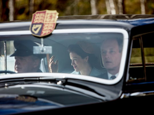 In a scene from Season 2 of 'The Crown,'  Claire Foy as Queen Elizabeth II waves to onlookers as she arrives at Balmoral.