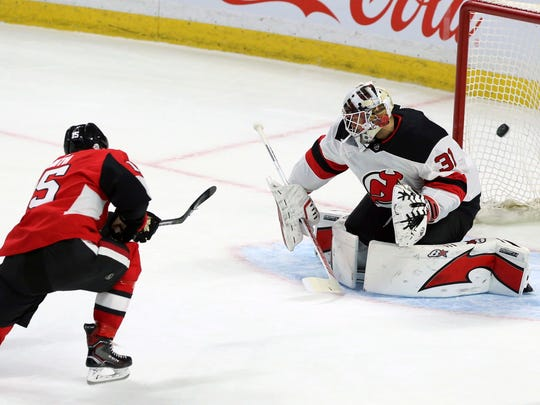 Ottawa Senators' Zack Smith (15) scores on New Jersey Devil goaltender Eddie Lack during his Devils' debut in the second period of an NHL hockey game Tuesday, Feb. 6, 2018, in Ottawa, Ontario.