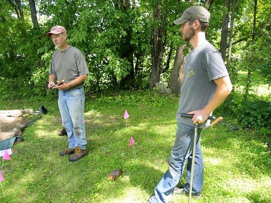 Rob Mann, assistant professor of anthropology at St. Cloud State University, on July 20, discusses with graduate student Jake Dupre the process used in searching for evidence of a stockade that historical records show once stood at the site in Fairhaven. The pink flags mark spots where anomalies were detected — potential sites to dig shovel test pits.
