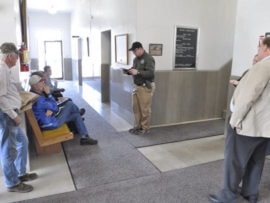 A small crowd listens as deputy U.S. Marshal Jeff Landers, center, reads the rules of a property auction at the Baxter County Courthouse on Wednesday. Landers was there auctioning off four properties owned by the late Dr. Stacey Johnson, whose fraud scheme involving Medicare and Tricare patients cost the U.S. Government some $14 million in phony medical bills.