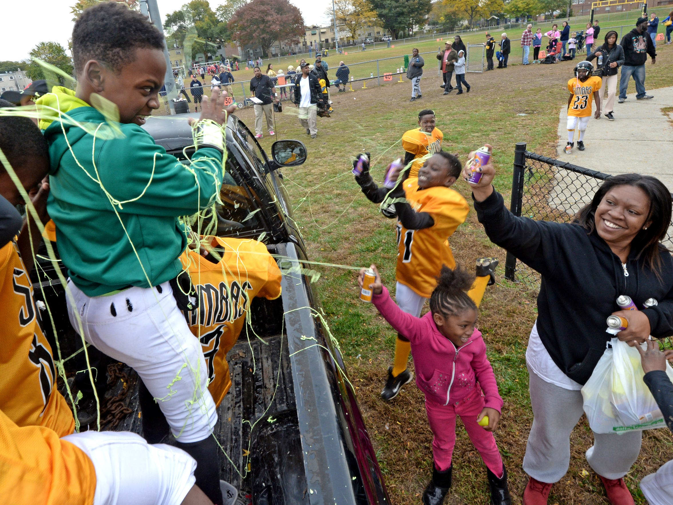 After beating Hamilton, Troy Lindsey Jr. and other Simbas get sprayed with silly string by Renekia Robinson and her daughter Janiyah Hill.