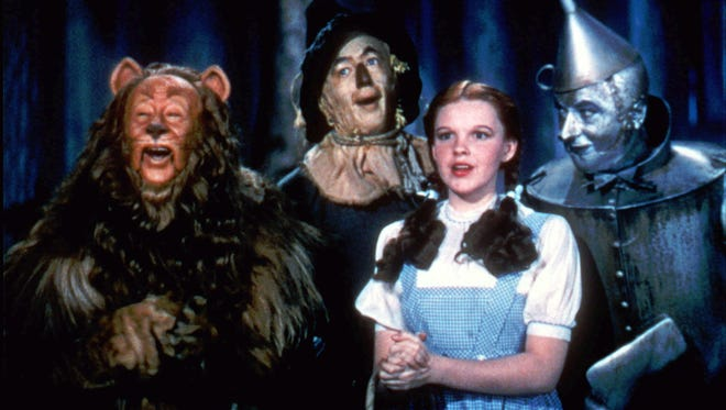Bert Lahr as the Cowardly Lion, Ray Bolger as the Scarecrow, Judy Garland as Dorothy, and Jack Haley as the Tin Woodman, in 'The Wizard of Oz.'