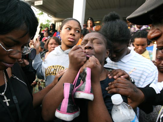 Mertilla Jones holds the shoes of granddaughter Aiyana Stanley-Jones at a candlelight vigil in 2010.