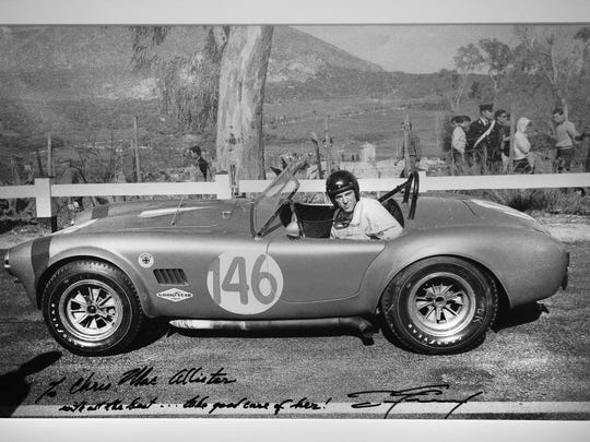A signed photograph of a 1964 Cobra race car once owned by driver Dan Gurney and now owned by Chris MacAllister hangs in his office. MacAllister, President of MacAllister Machinery in Indianapolis and vintage race car owner and enthusiast, not only enjoying the cars in his collection but how much he loves racing them all over the world. MacAllister will have his vintage cars are part of the event at Indy Motor Speedway this weekend.