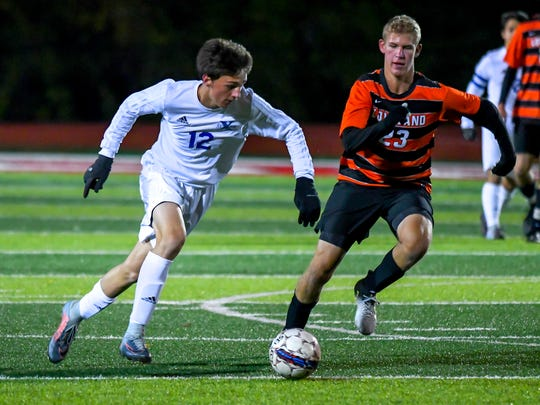 St. X junior Gino Geiser (12) dribbles the ball past Loveland's Keith Broermann (23) in OHSAA tournament at Princeton High School, Saturday, Oct. 28, 2017