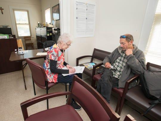 15-year volunteer Mary Bond, left, checks in new patient