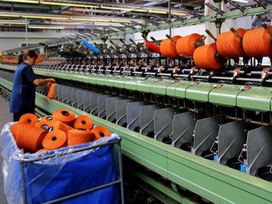In this photo taken June 29, 2016, bright orange yarn is set up on a machine at the Johnsons of Elgin wool mill in Elgin, in the Speyside region of Scotland. Johnsons, known for luxury cashmere, offers mill tours and has a cafe and gift shop on site.