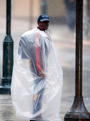 A man covered in plastic waits to cross 19th Street during a rainstorm Wednesday, Oct. 15, 2014, in Philadelphia. (AP Photo/Matt Rourke)