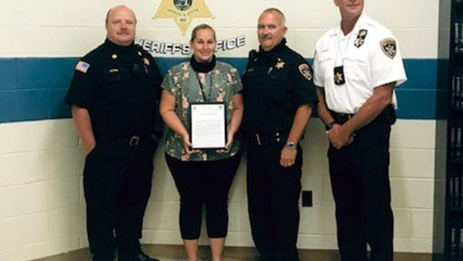 Melissa Hale, second from left, recently received a special commendation from Madison County Sherriff Todd Hood, far right, for her work to support Madison County Jail inmates during the pandemic. With them are Capt. Timothy Flynn and Sgt. Jon Black.