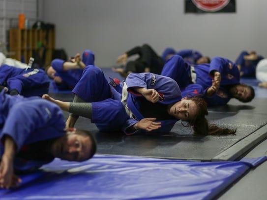 Students warm up during a jiu-jitsu class at Gracie Barra Las Cruces Brazilian Jiu-Jitsu and Self-Defense.