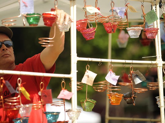 Kevin Reuter of Mayville helps hang bird feeders during the 22nd annual Garden Fair in Washington Park in 2012.