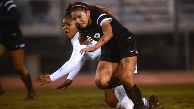 Oxnard's Nina Watson (left) keeps her eye on the ball as she loses her footing in the mud to Pacifica's Audrey Castillo during Thursday's Pacific View League soccer game.