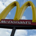 A former McDonald's worker acquitted of charges he placed shards of glass into a police officer's Big Mac nearly a decade ago has won a settlement.