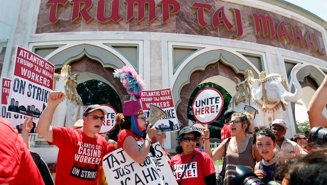 Striking workers shout and hold signs as they picket outside the Trump Taj Mahal hotel in October. Owner Carl Icahn closed the casino, and now the New Jersey Senate has voted to penalize Icahn for his action.