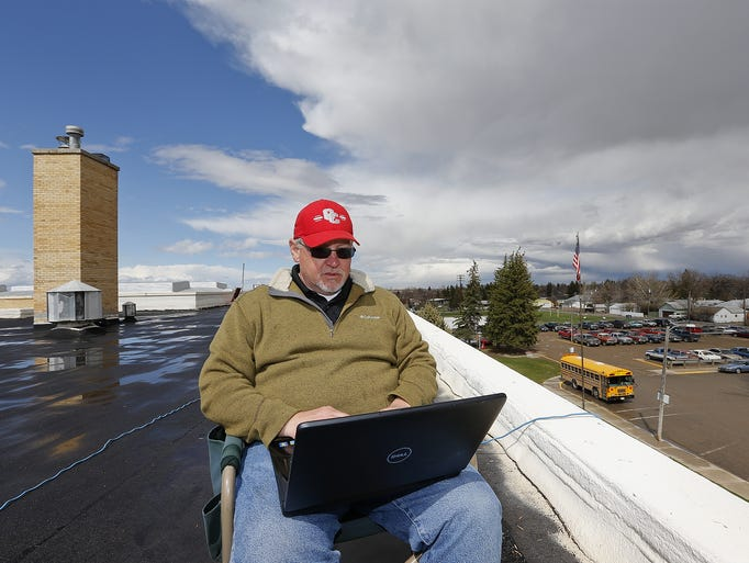 Conrad High School principal Ken Larson uses a laptop computer as he spends time on the roof of the high school after the school collected 442 items of food for the Pondera County Food Bank. Larson spent one minute on the roof for each item of food. TRIBUNE PHOTO/LARRY BECKNER