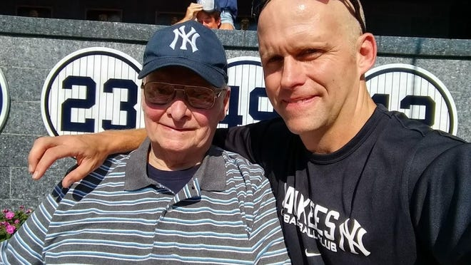 Tim Cox, right, enjoys a moment with his dad, Woody Cox, at Yankee Stadium in 2017.