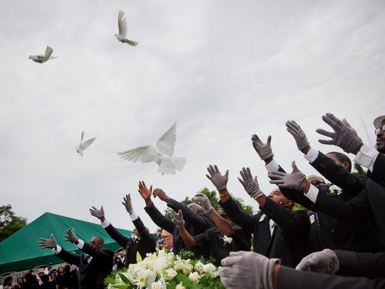 Pallbearers release doves over the casket of Ethel
