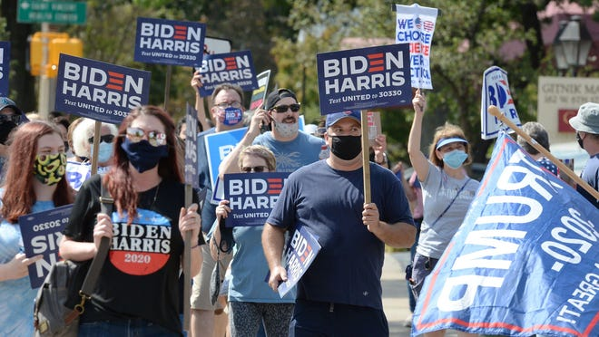 People in support of Democratic presidential candidate Joe Biden and running mate Kamala Harris, pass a few Donald Trump supporters, right, on Sept. 26, 2020, in Erie, Pennsylvania. More than 50 people joined the 'Blue Wave Across Sixth Street' organized earlier online.