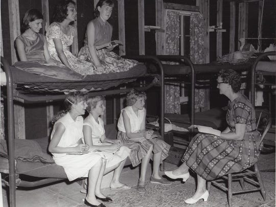 A woman reads a Bible passage to children in a summer camp.