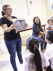 Kindergarten teacher Bri Flores shows her students one of the many literary projects, created by other students at Saint Francis School, during the Young Authors and Illustrators Fair in Yona on Friday, Nov. 13. The event was held with an emphasis on literacy development amongst the students.