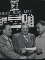 Milwaukee County formally gets the keys to the scoreboard at County Stadium before the Milwaukee Braves-New York Giants game on May 12, 1953. Milton J. McGuire (from left), president of the Milwaukee Common Council and Miller Brewing Co. president Frederick C. Miller (right) shake hands, as Miller hands, Gerald H. Kops, vice chairman of the County Board, some paperwork. Miller Brewing paid for the $75,000 scoreboard in return for advertising rights. This photo was published in the May 13, 1953, Milwaukee Journal.