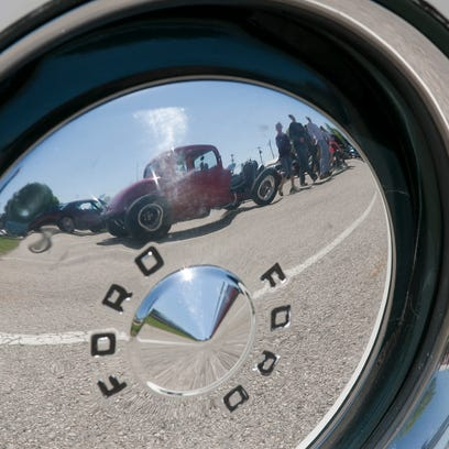 A 1930s hotrod is reflected in the early 1950s Ford hubcap at the Plymouth High School automotive technology class sponsored car show Friday May 22, 2015 at Plymouth.