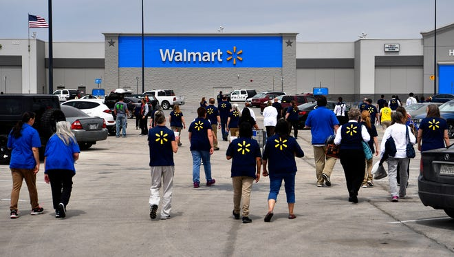 Walmart employees return to the north side store after being given the all-clear Friday April 6, 2018. A bomb threat had been called in after the lunch hour and employees and customers were evacuated to the far side of the parking lot.