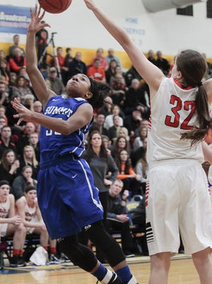 "Ravin Alexander of Summit Country Day tries an unorthodox shot to get over 6'2"" Danielle Winner of Versailles."