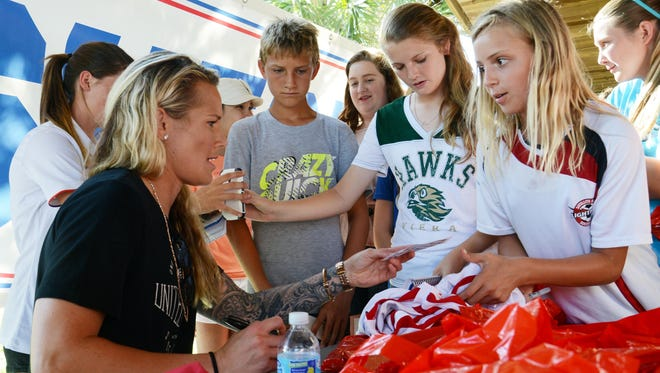 U.S. Women's National Soccer Team goalkeeper Ashlyn Harris, left, signs autographs for her fans May 19 during a celebration of her career at Pelican Beach Park in Satellite Beach.